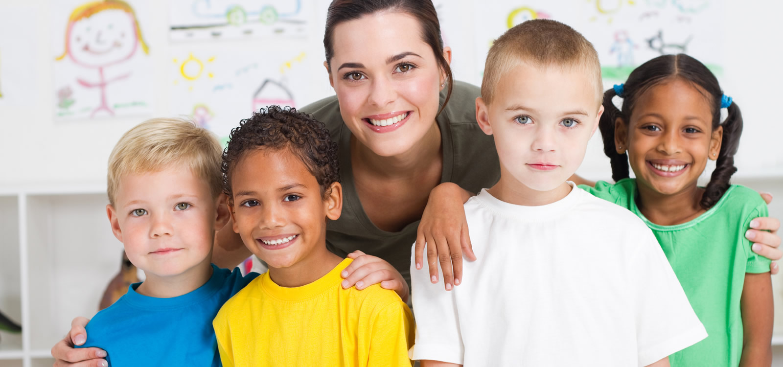 Smiling female teacher with her arms around 4 children